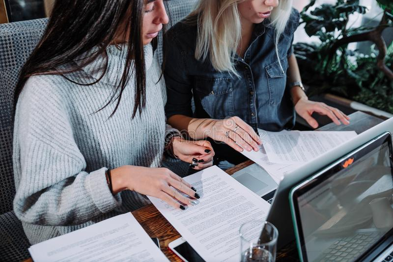 Young girls sitting in cafe using laptop . Girl showing her friend something on laptop. Two businesswoman working together about documents, partner discuss plan stock images