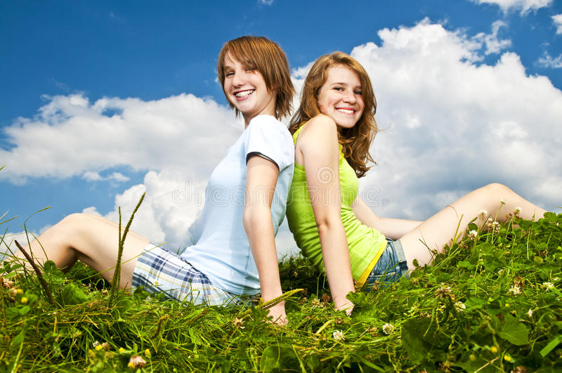 Download Young Girls Sitting In Meadow Stock Photo - Image: 12568934