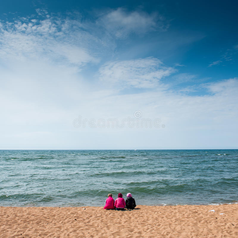 Young girls sitting on the shore of the lake Baikal in the summer. stock images