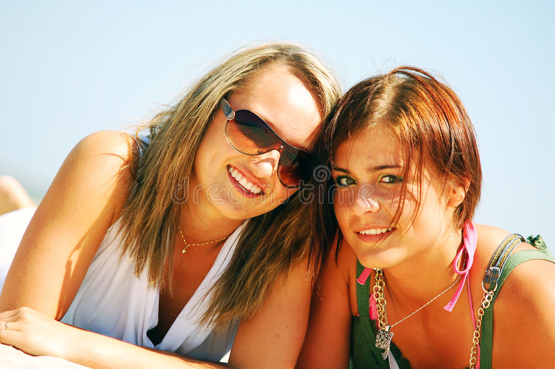 Young girls on the summer beach. Young attractive girls enjoying together the summer beach royalty free stock photos