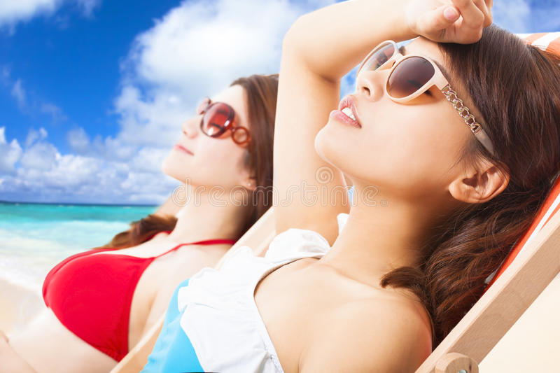 Young girls sunbathing and lying on a beach chair. Young girls sunbathing and lying on a chair with beach background stock photos