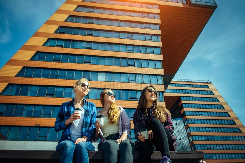 Young girls in sunglasses sitting on a city street and drink coffee to take away. Three cute women have a coffee break together royalty free stock photo