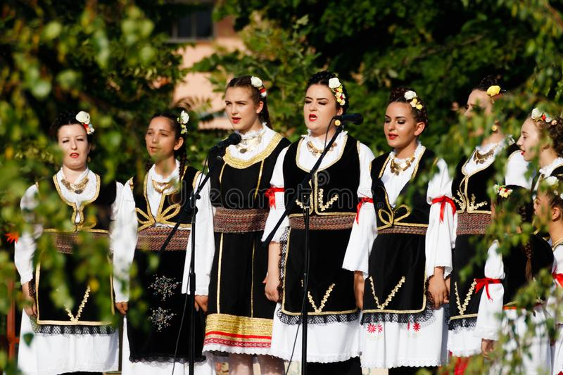 Young girls in traditional costumes singing in a parade in Vojvodina stock images