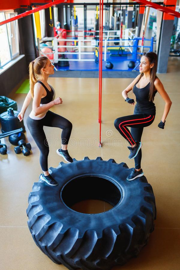 Young girls train on the big tire in the gym. royalty free stock photos