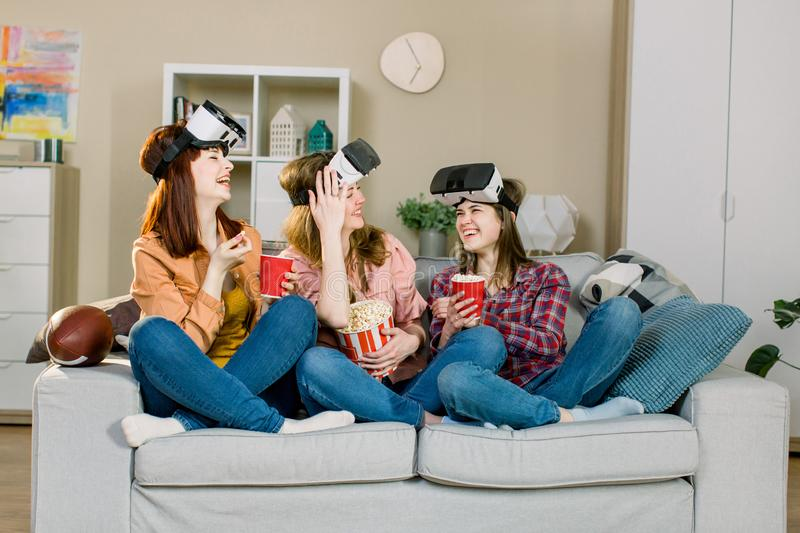 Young girls wearing virtual reality glasses indoor - Happy people having fun with new technology vr headset goggles - stock photo