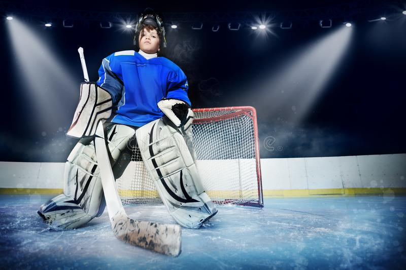 Young goalie in the spotlight of ice hockey arena. Low-angle portrait of young goalie, teenage boy in protective equipment, standing next to the net in the royalty free stock photos