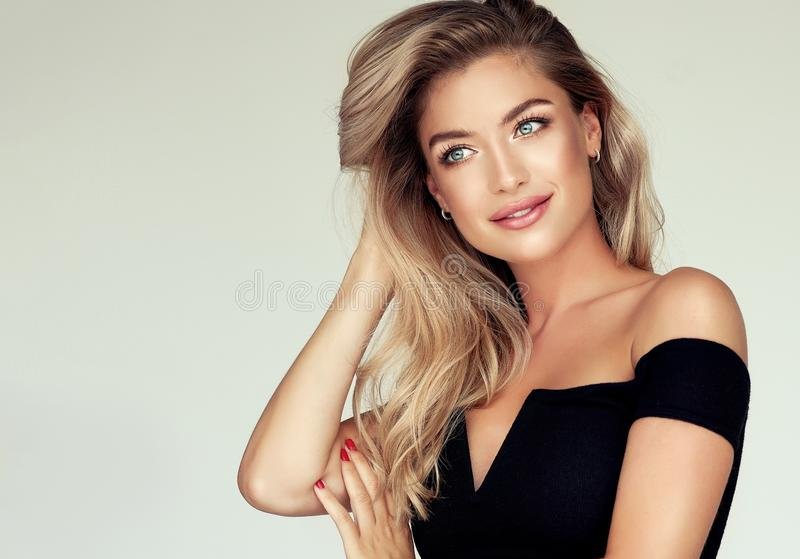 Portrait of gorgeous young woman with elegant make up and perfect golden hairstyle. Young golden haired pretty model tenderly looking aside with light smile and stock photos