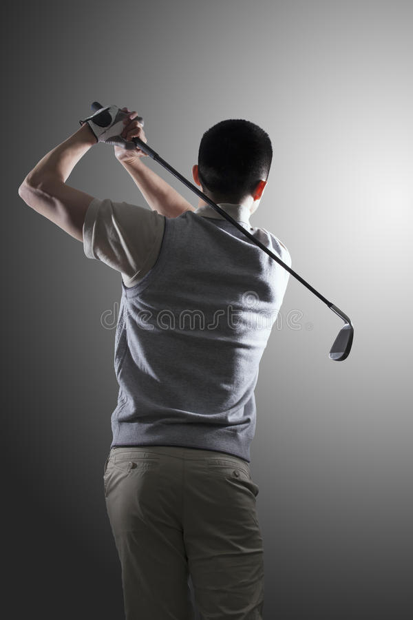Young golf player swinging, rear view royalty free stock photo