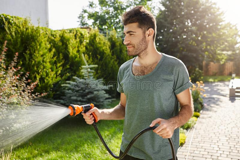 Young good-looking bearded caucasian man with stylish hairstyle in blue t-shirt concentrated watering garden with hose. stock photo