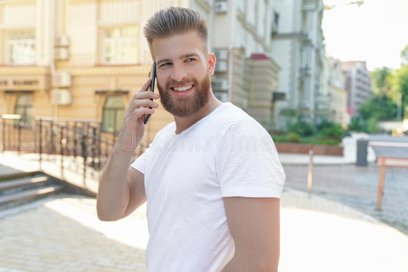 Young good looking bearded guy is sitting outdoors in front of his house talking on the phone and smiling royalty free stock photo