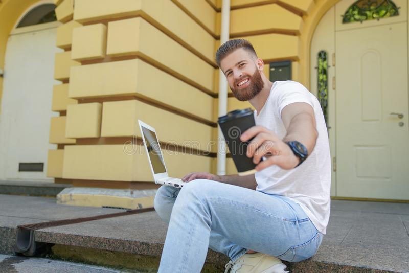 Young good looking bearded guy is sitting outdoors on stairs in front of his house working on laptop. he is smiling and drinking royalty free stock photos
