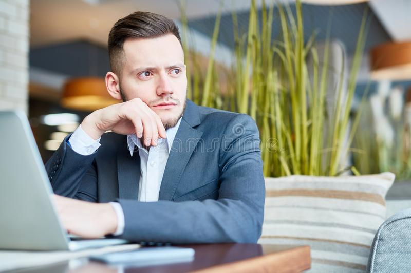 Abstracted businessman in cafe. Young good-looking Caucasian male entrepreneur sitting at cafe table with laptop and looking out the window thoughtfully royalty free stock photos