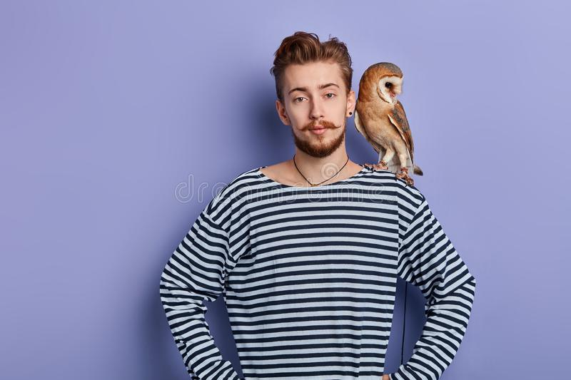 Young good looking man holds a predatory tamed owl on his shoulder. Close up portrait. isolated blue background, studio shot, bird lover, friendship royalty free stock image