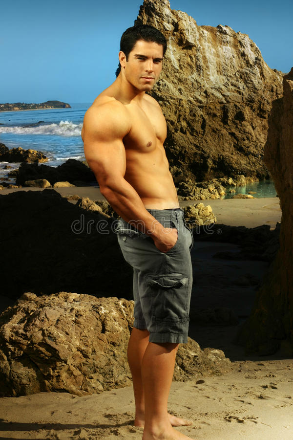 Young goodlooking fitness male model at a beach royalty free stock photo