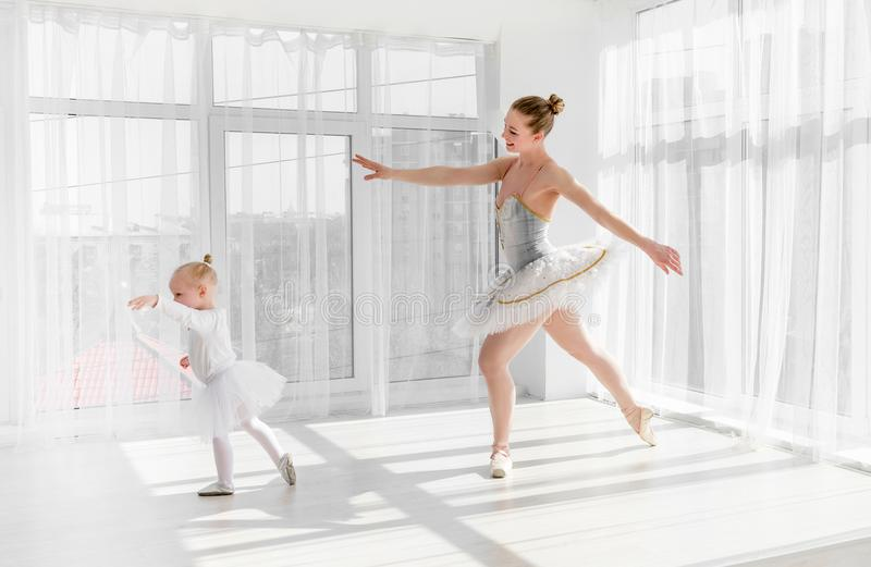 Young gorgeous ballerina with her little daughter dancing in studio royalty free stock image