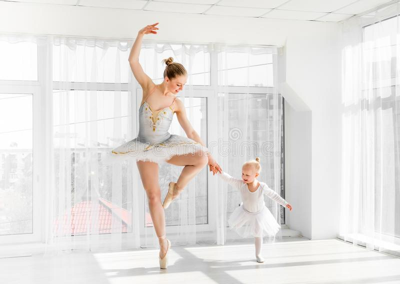 Young gorgeous ballerina with her little daughter dancing in studio stock photography