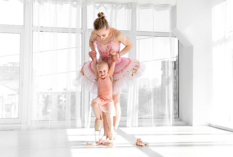 Young gorgeous ballerina with her little daughter dancing in studio stock images