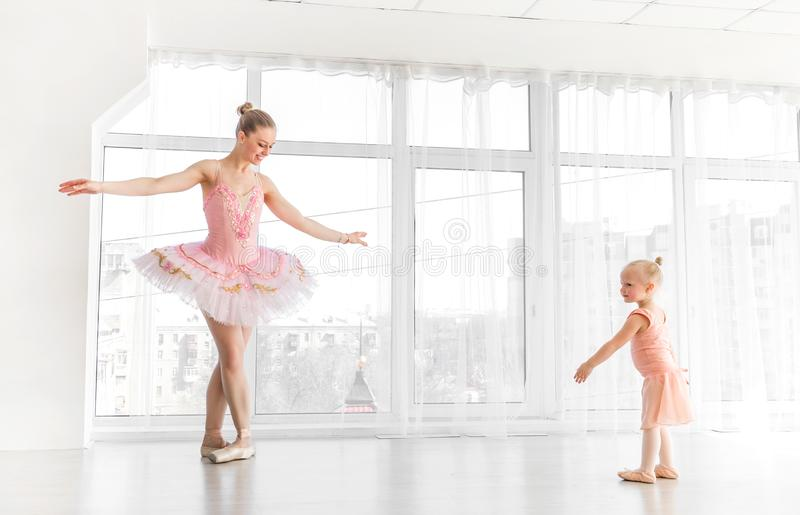 Young gorgeous ballerina with her little daughter dancing in studio stock photo