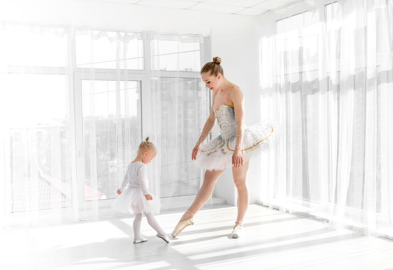 Young gorgeous ballerina with her little daughter dancing in studio royalty free stock images