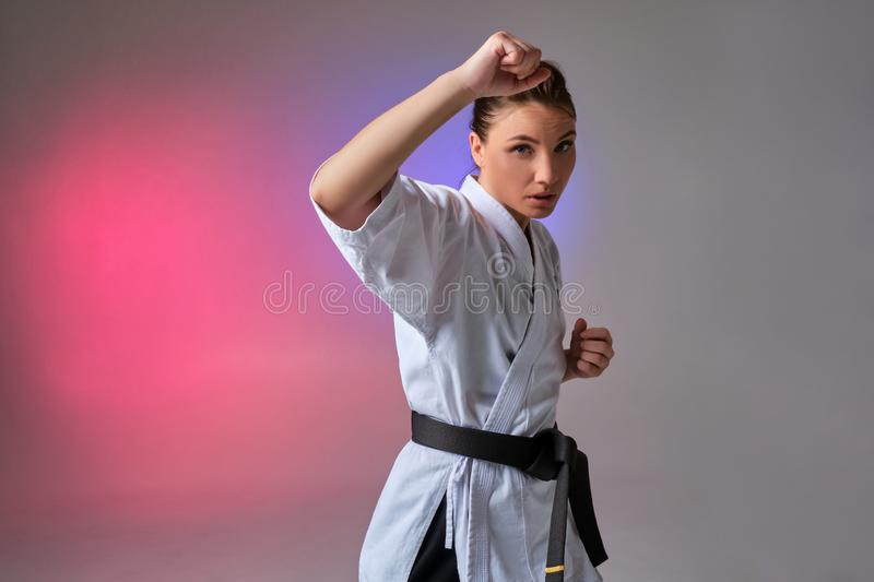 Athletic woman in traditional kimono is practicing karate in studio. Young gorgeous girl with ponytail hair, dressed in a traditional kimono is looking at you stock image