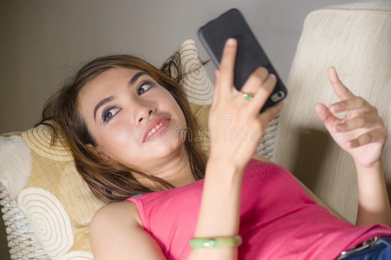 Young gorgeous and happy hispanic woman lying on home sofa couch. Using internet app on mobile phone sending text relaxed and smiling thoughtful in royalty free stock images