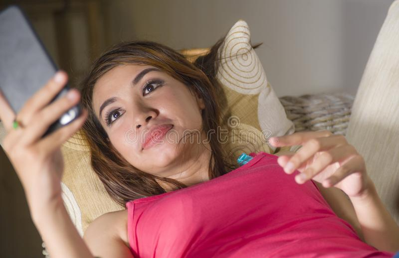 Young gorgeous and happy hispanic woman lying on living room sofa couch. Young gorgeous and happy hispanic woman lying on home sofa couch using internet app on royalty free stock photo