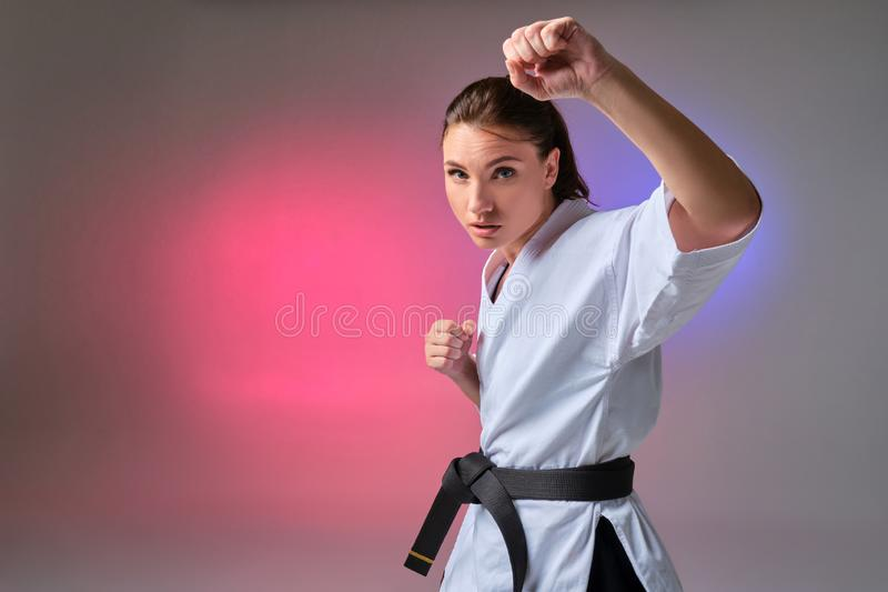 Athletic woman in traditional kimono is practicing karate in studio. Young gorgeous lady with ponytail hair, dressed in a traditional kimono is practicing stock photos