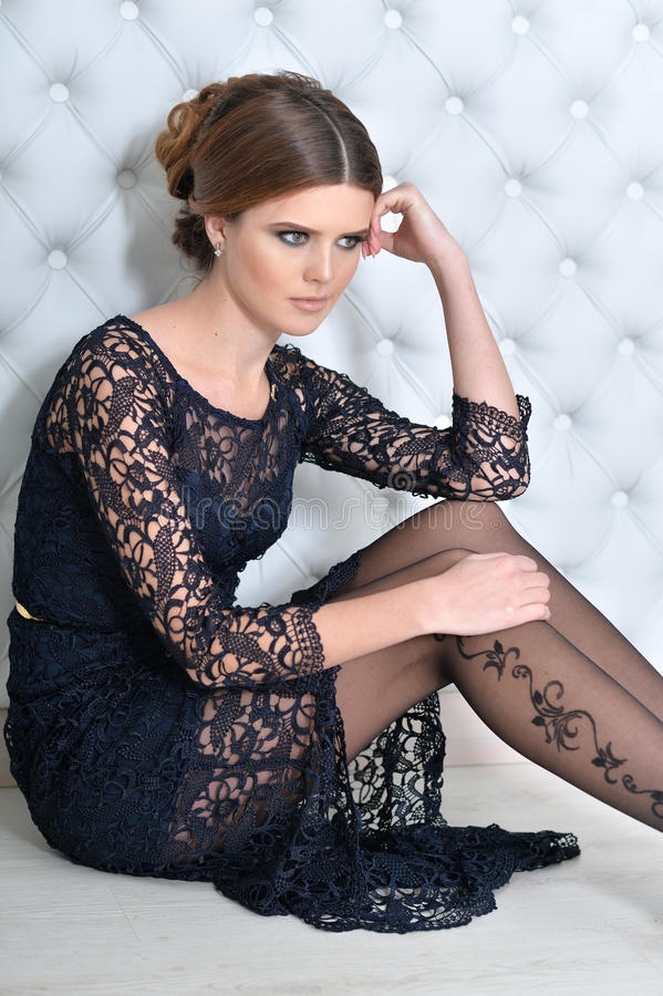 Young gorgeous woman in black dress. With beautiful make-up and hairdo royalty free stock photos