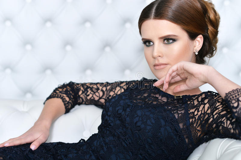 Young gorgeous woman in black dress. With beautiful make-up and hairdo stock images