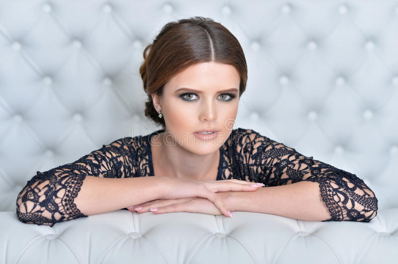 Young gorgeous woman in black dress. With beautiful make-up and hairdo royalty free stock photo