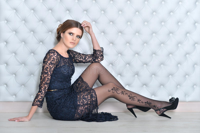 Young gorgeous woman in black dress. With beautiful make-up and hairdo stock photo