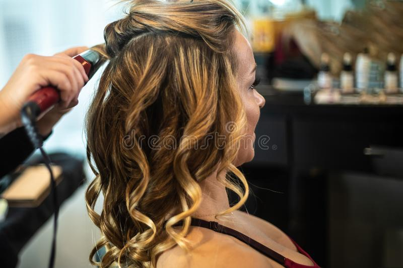 Young Gorgeous Woman Getting Hair Curled. At High-End Hair Salon stock images