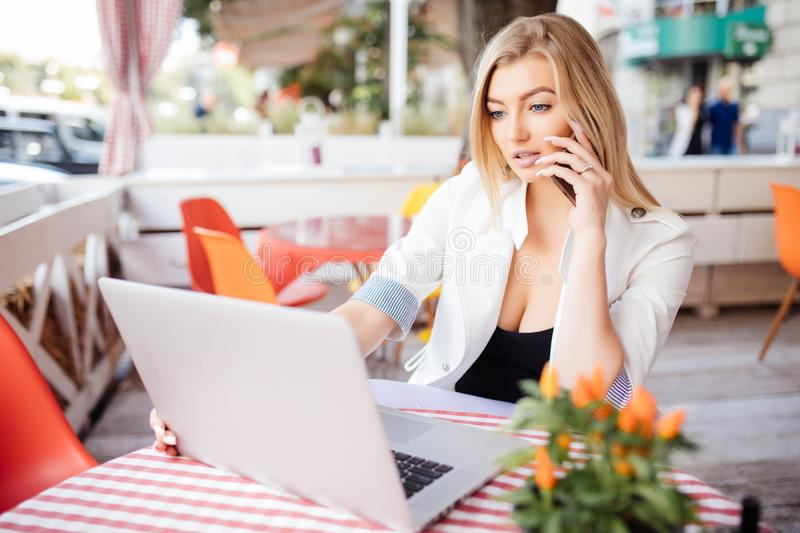 Young gorgeous woman having smart phone conversation while sitting in front of open laptop computer in cafe bar, attractive female stock photo