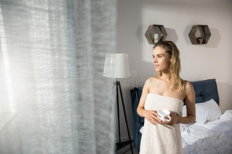 Young gorgeous woman wrapped up with bath towel standing with coffee stock photography