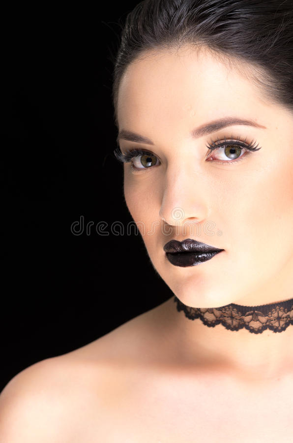 Young gothic beautiful woman. Closeup portrait of young gothic beautiful woman with black makeup stock image