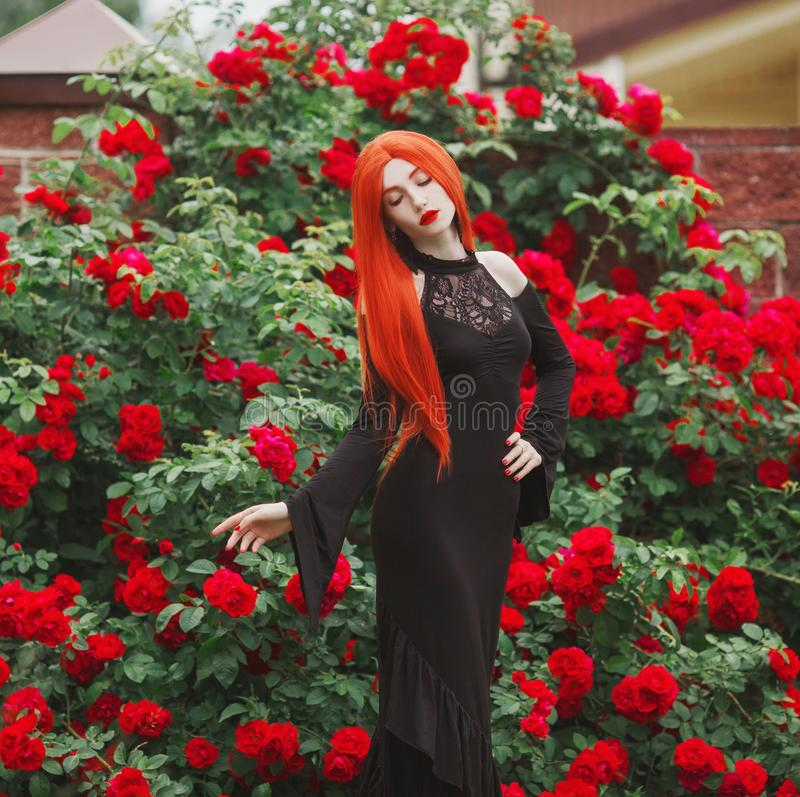 Young gothic girl with red lips in black magnificent dress on dark background. Redhead pale model on background of roses bush. stock photography
