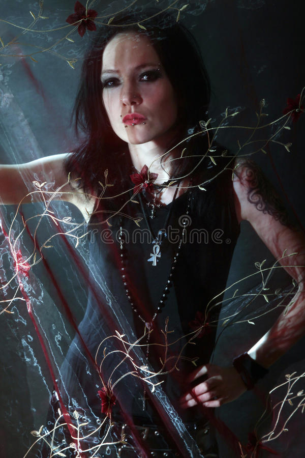 Young gothic woman. Gothic woman behind the curtain stock image
