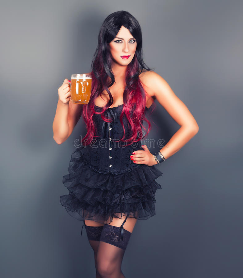 Young gothic woman in corset. With mug of beer in hand royalty free stock images