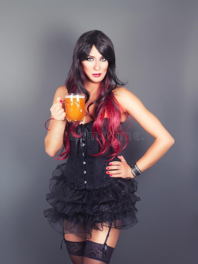 Young gothic woman in corset. With mug of beer in hand stock image