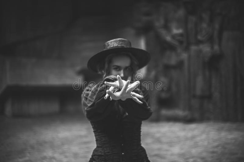 Young gothic woman pulls hands, black and white. Focus on female hands, dark background stock photo