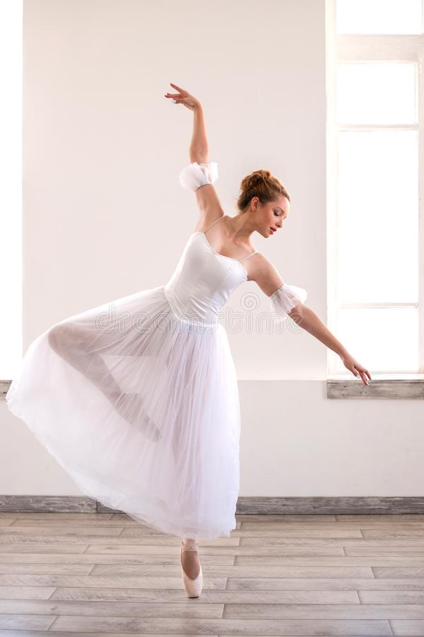 Young graceful ballerina dancing on white studio. royalty free stock photo