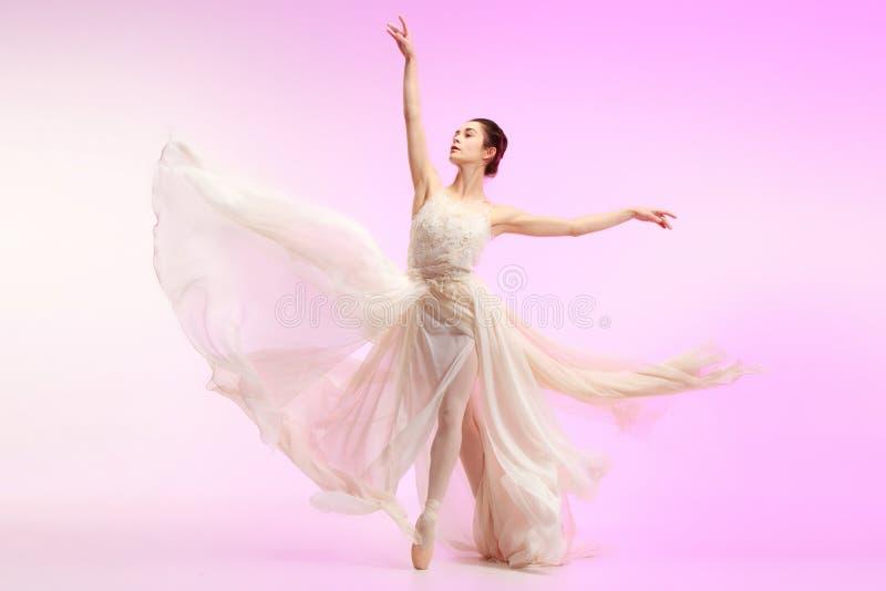 Ballerina. Young graceful female ballet dancer dancing over pink studio. Beauty of classic ballet. royalty free stock photo