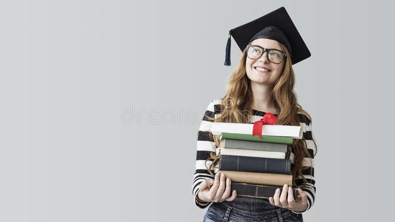 Young graduated student looking away and carrying books on gray background stock image