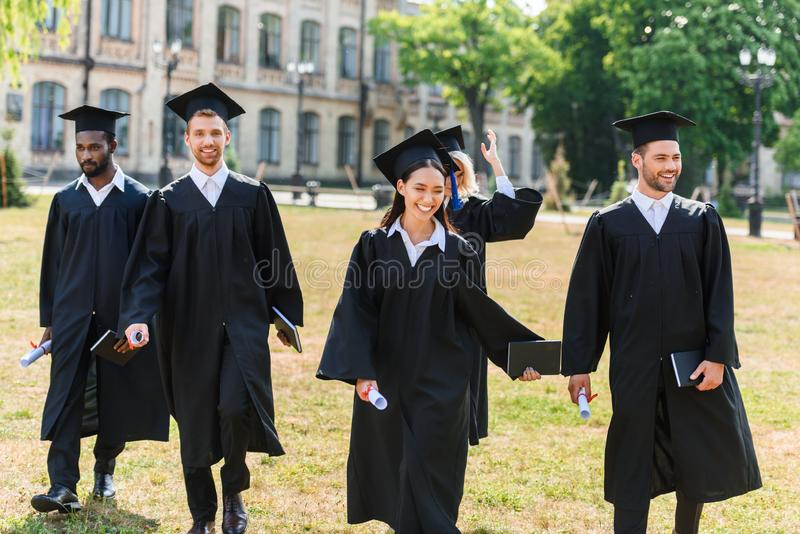 young graduated students in capes walking royalty free stock photography