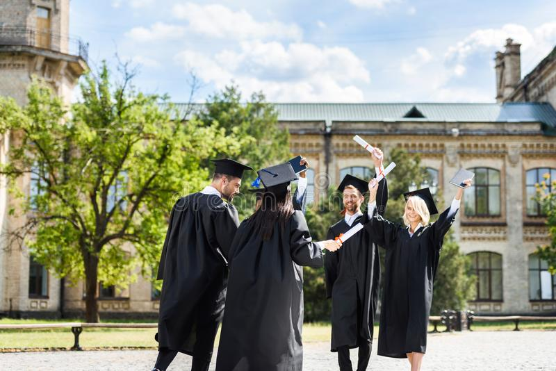 young graduated students with diplomas greeting each other stock photos