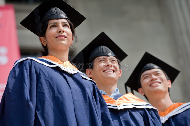 Young Graduates. Three young graduates standing outdoors in graduate attire royalty free stock image