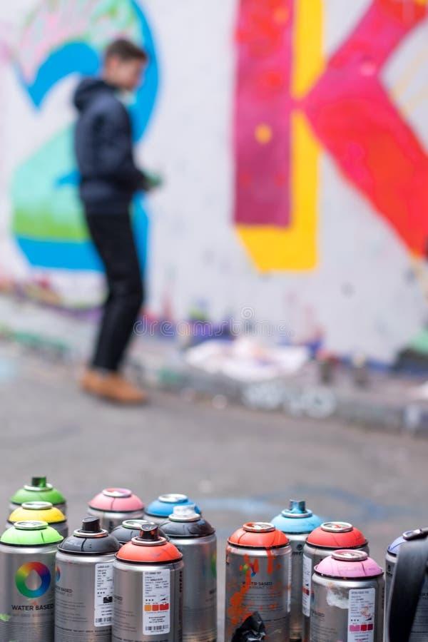 Young graffiti artist at work blurred, Leake Street tunnel. Waterloo, London UK. royalty free stock photography