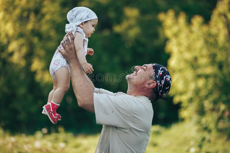 Young grandfather playing with adorable baby girl over a nature background. Grandparents and grandchild leisure time concept. Senior men playing with adorable royalty free stock image