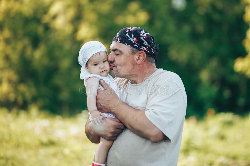 Young grandfather playing with adorable baby girl over a nature background. Grandparents and grandchild leisure time concept. Senior men playing with adorable royalty free stock photo