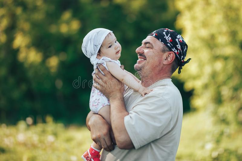 Young grandfather playing with adorable baby girl over a nature background. Grandparents and grandchild leisure time concept. Senior men playing with adorable stock photos